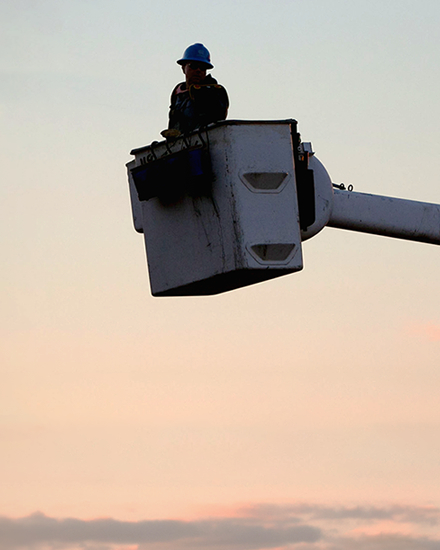A Con Edison employee in a bucket truck, with a sunset in the distance.