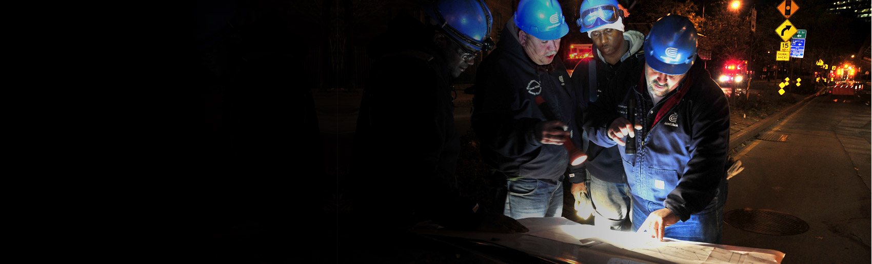 Con Edison workers with flashlights are viewing documents in a darkened city street.