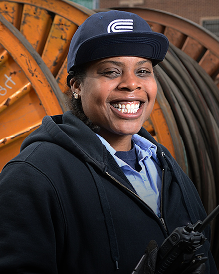 A Con Edison employee is warmly smiling, with a large reel of cable in the background.