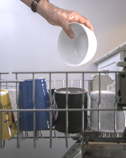 Dishes being loaded into a dishwasher