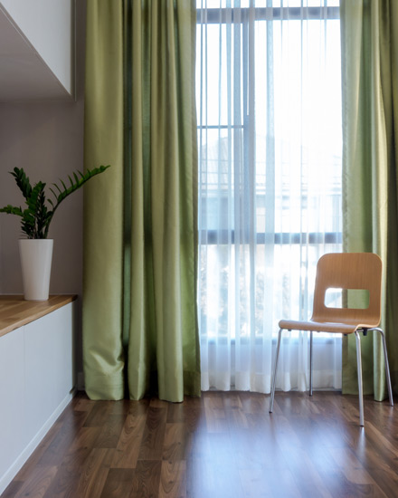 Sunny windows framed with green drapes.
