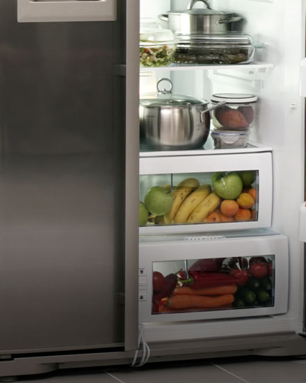 An open refrigerator door is fully stocked with fruits and vegetables.