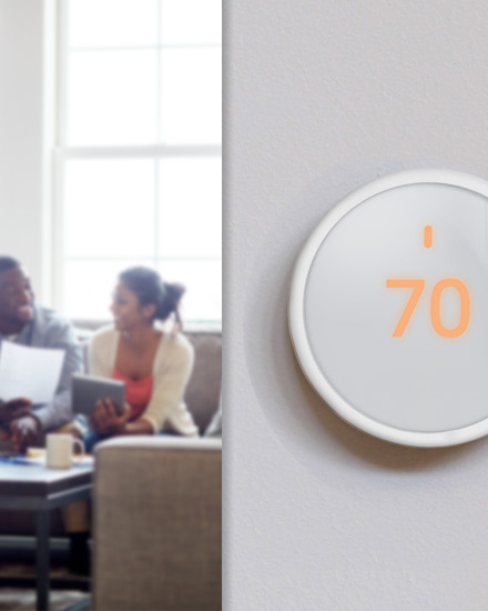 A couple sits in a cozy living room, with a detailed view of a smart thermostat on the wall.