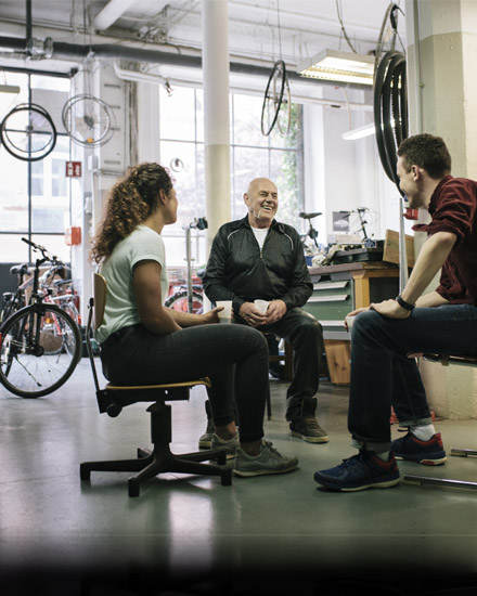 Three people are having a discussion in a bike shop.