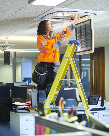 Two works are installing energy-efficient overhead lighting, in an office setting.