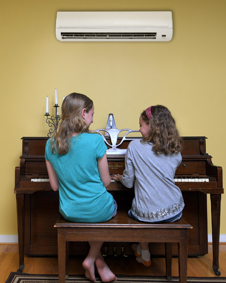 Two girls are playing the piano with a mini-split mounted on the wall above them.