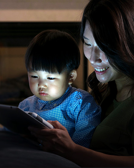A mother and child are reading from a tablet screen.