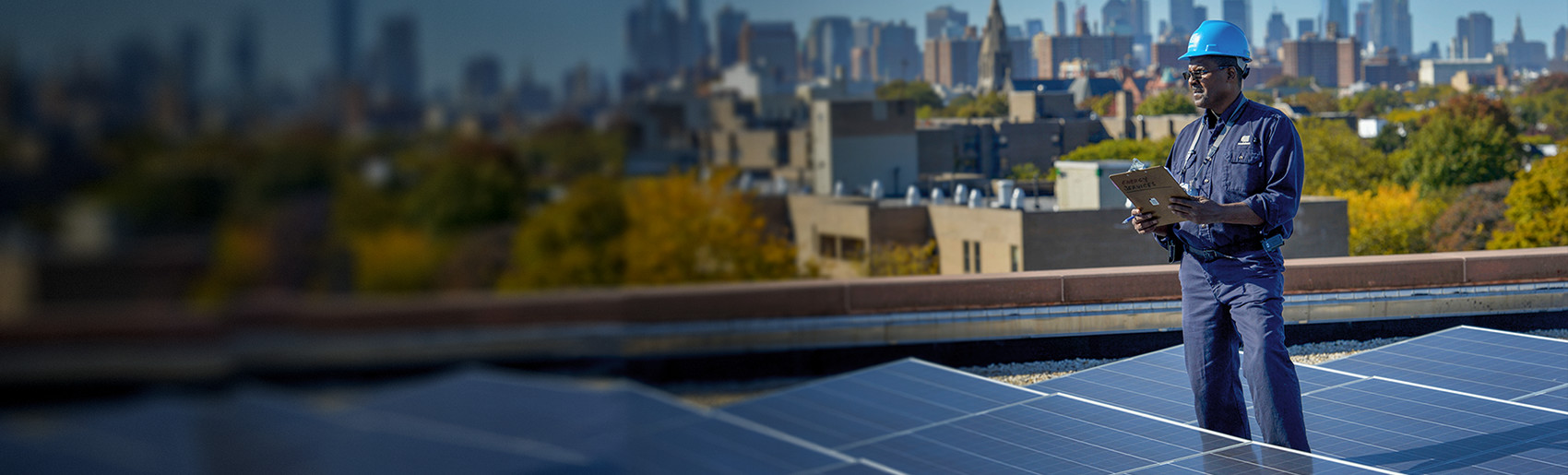 A Con Edison employee standing amid a rooftop solar installation.