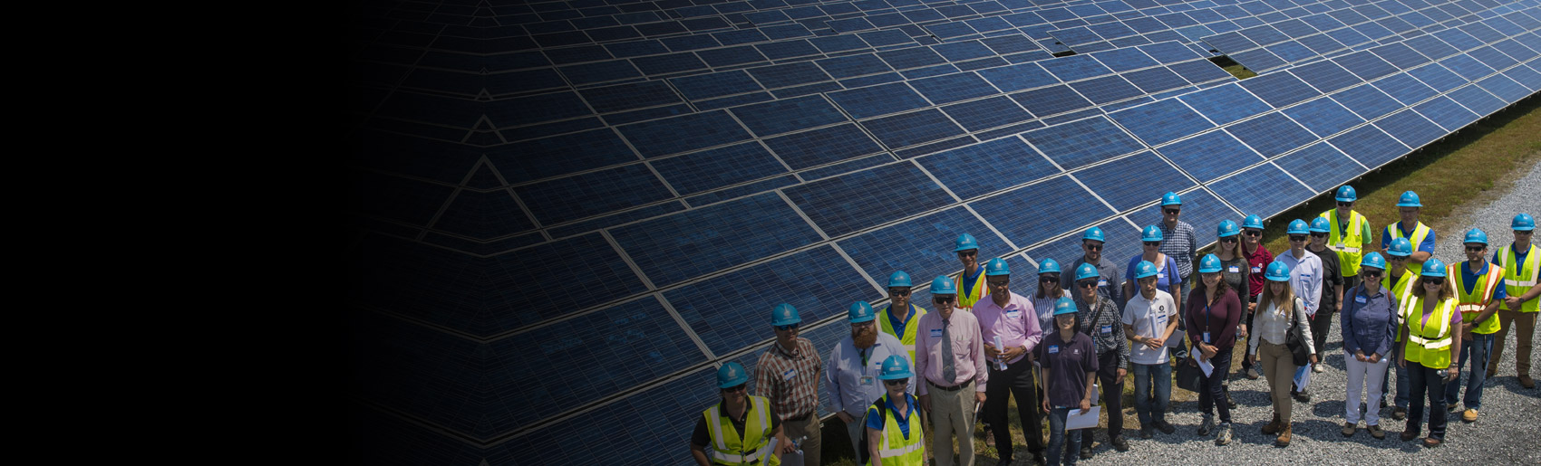 A team of Con Edison employees standing near a large solar panel installation