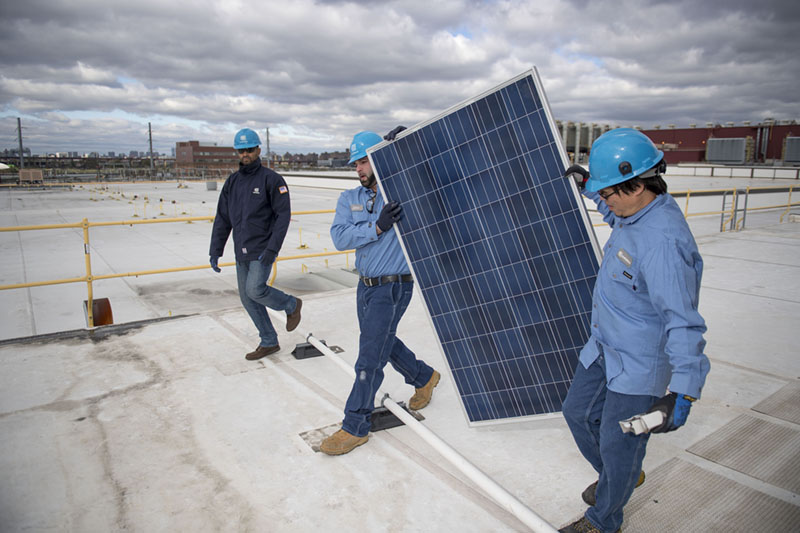Two man carrying a solar panel for an installation