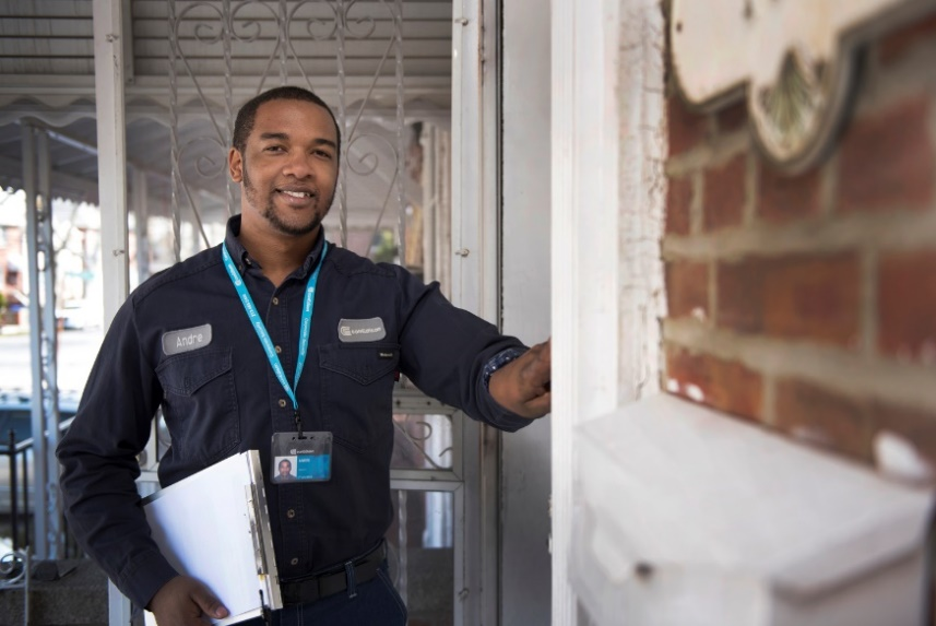 A Con Edison employee wearing a company ID, ringing a doorbell.