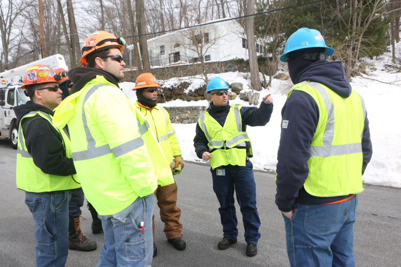 A group of crew members in yellow safety vests are standing near a snow-covered slope, assessing site conditions.