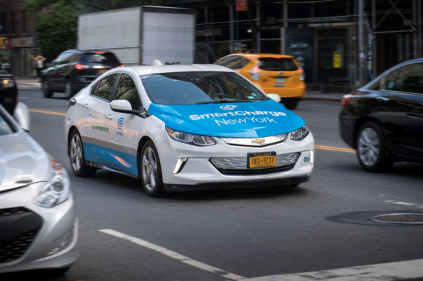 A electric sedan with Con Edison and Smart Charge logos, is driving through midtown in New York City.