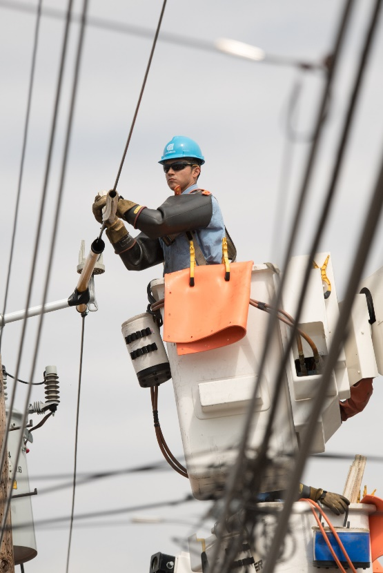 A Con Edison crew member working in a bucket truck on reconnecting above-ground electrical power.