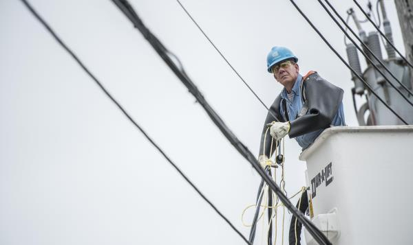 A Con Edison employee working on overhead power lines.