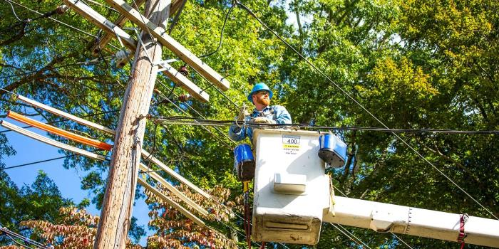 A Con Edison employee is working to repair outside power lines.