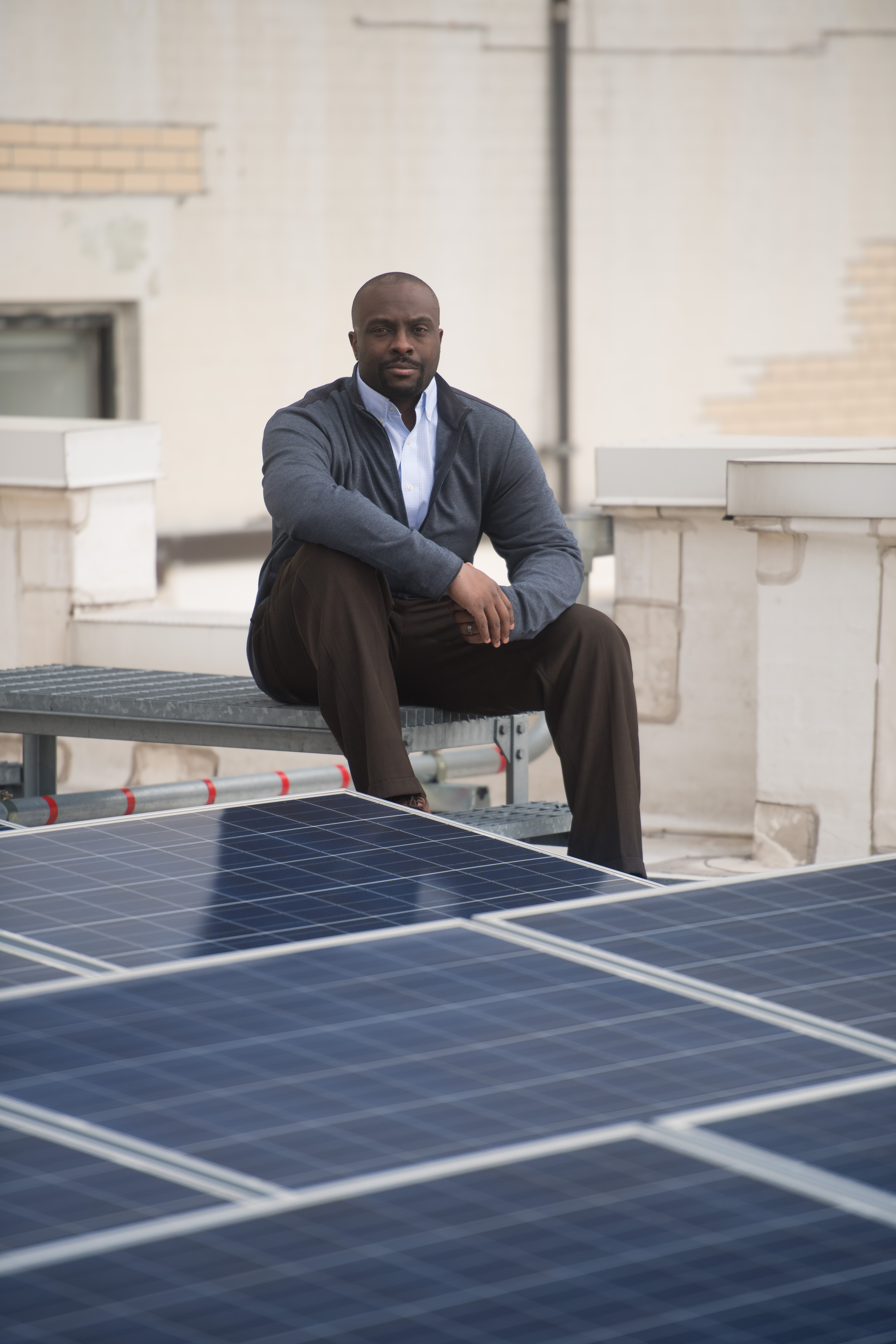 Andrew Ried, a Con Edison employee, near a solar panel installation.