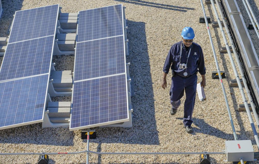 A Con Edison employee walking across a rooftop installation of solar panels.