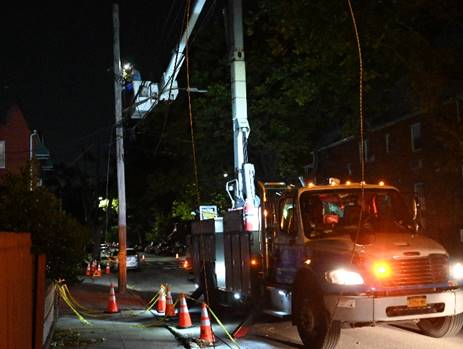 A worker in an overhead bucket truck making repairs during the night.