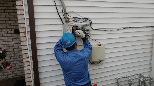 A worker installing a smart meter on an exterior wall.