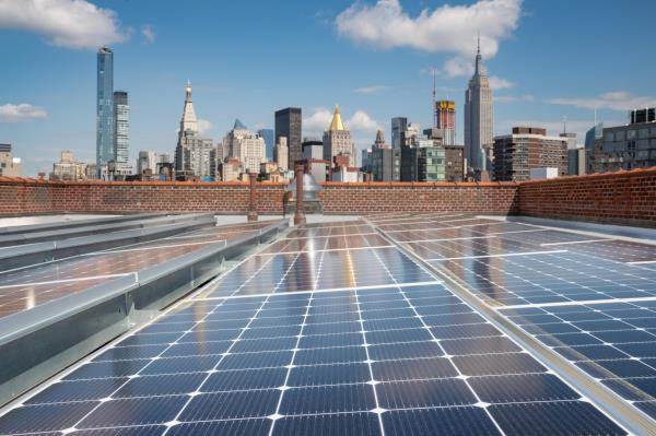Solar panels on a rooftop with the New York City skyline in the background.