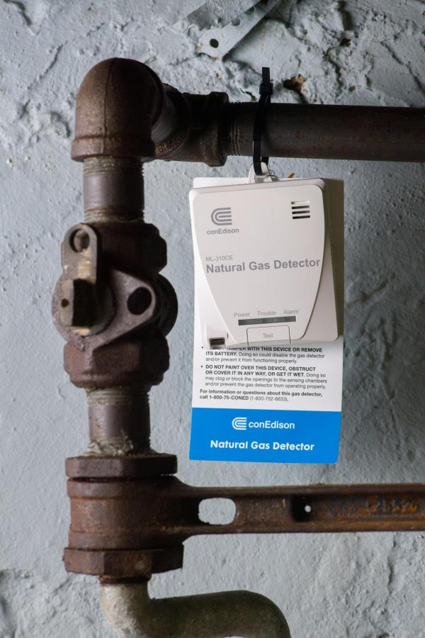 A gas detector hangs from a pipe.