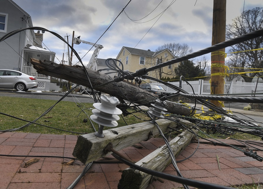 An overhead power line has fallen into a front yard