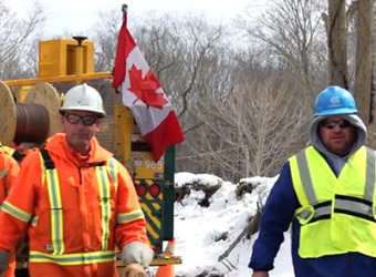 a Canadian Mutual Aid utility worker and a Con Edison worker on a snowy worksite with Canadian flag in the background