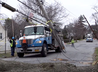 Utility truck and workers securing broken telephone poles that are broken and knocked over in the street with wires down