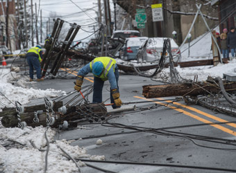 Con Edison utility workers cutting wires of multiple downed telephone poles lying across the street
