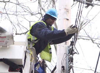 Con Edison utility worker fixing wires on a telephone pole