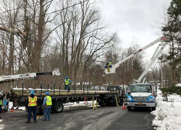 Con Edison work trucks on a snow-covered street repairing damage after the Riley-Quinn storm events.