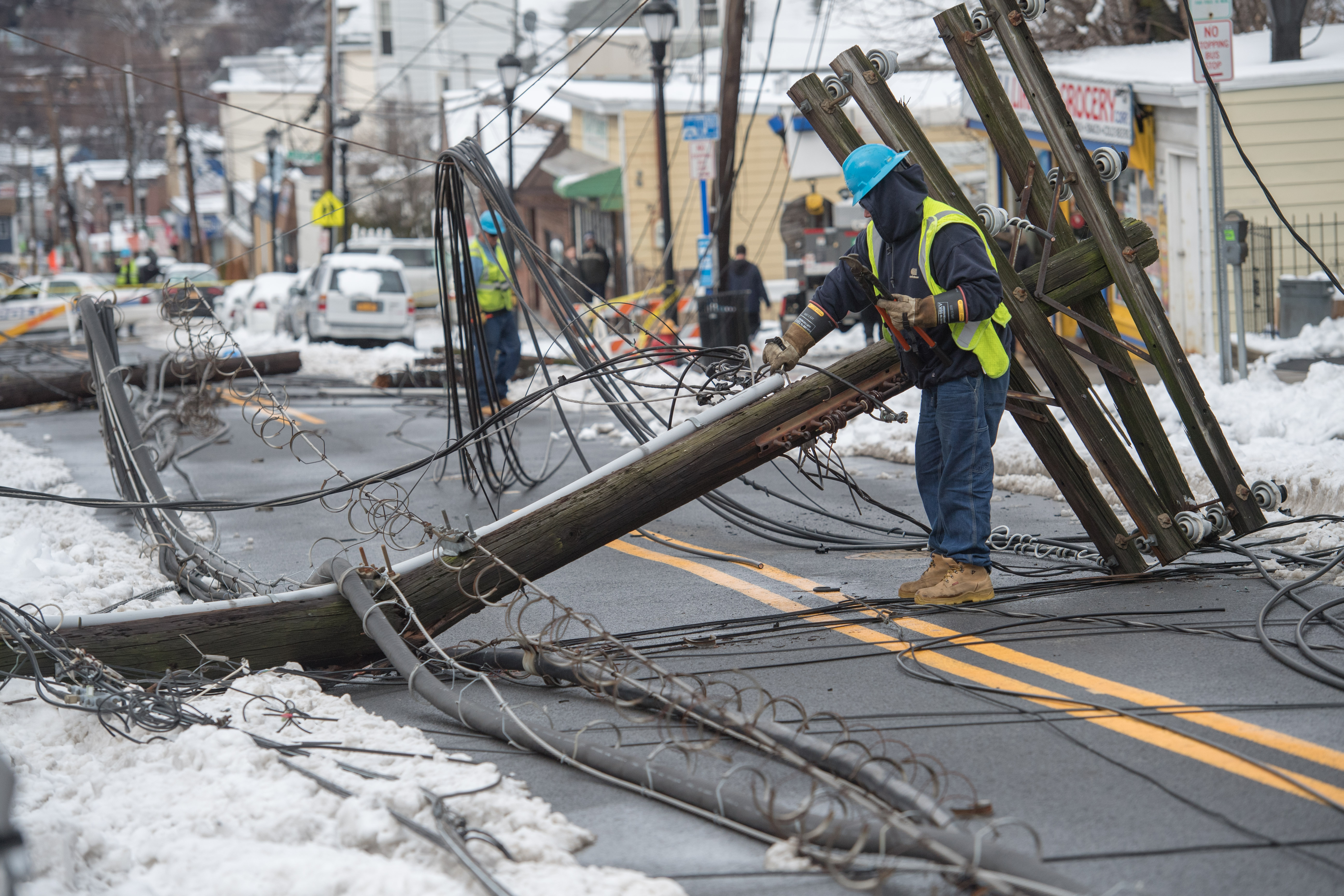 A worker repairing overhead power lines damaged during the Riley-Quinn storm events.