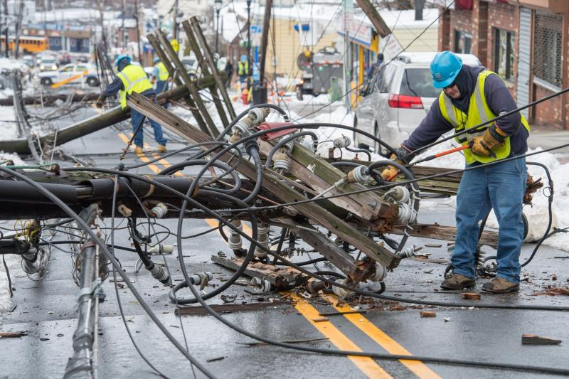 A Con Edison employee is working to damage to a fallen power pole.