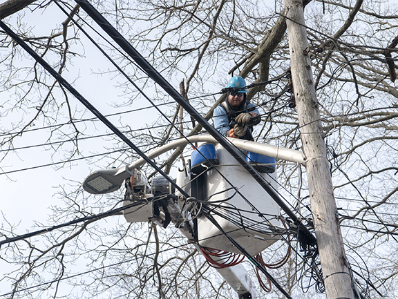 Con Edison crew member working to restore power to a utlilty pole.