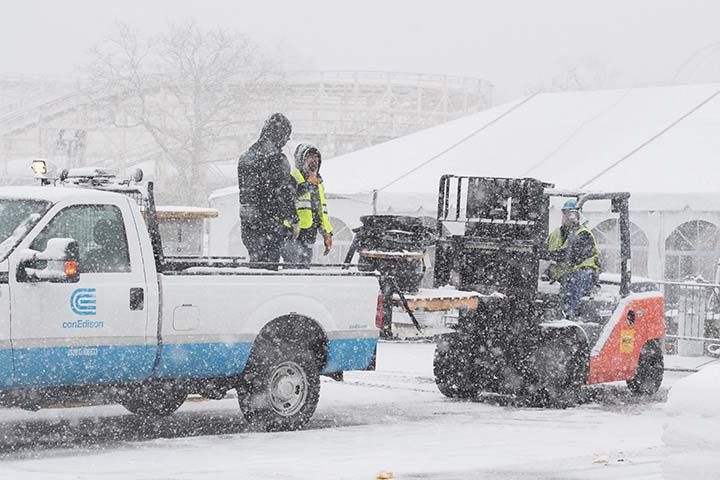 While snow is falling, Con Edison workers are unloading supplies to assist with the Riley-Quinn restoration efforts.