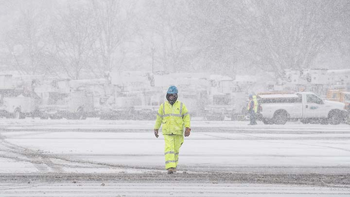 A Con Edison worker is walking through a snow covered recovery staging area.
