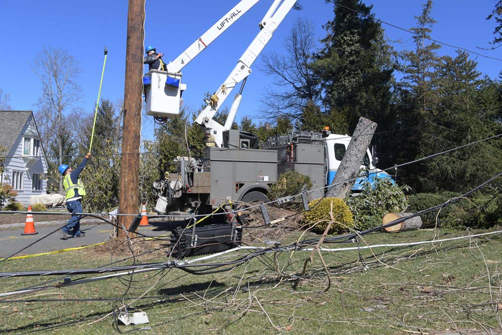 A worker in a bucket truck is repairing damage to overhead poles after the Riley-Quinn storm events.