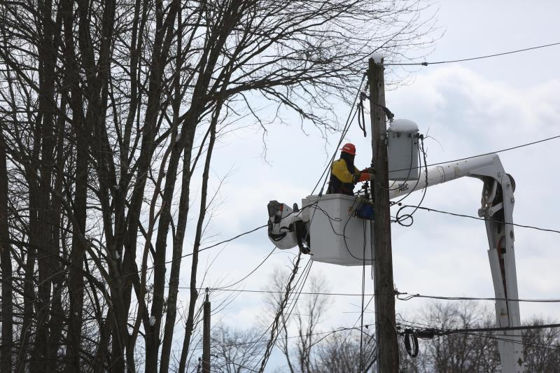A Con Edison worker is working to restore power to overhead lines.