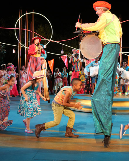 A troupe of young performers on a stage, in a circus-link setting