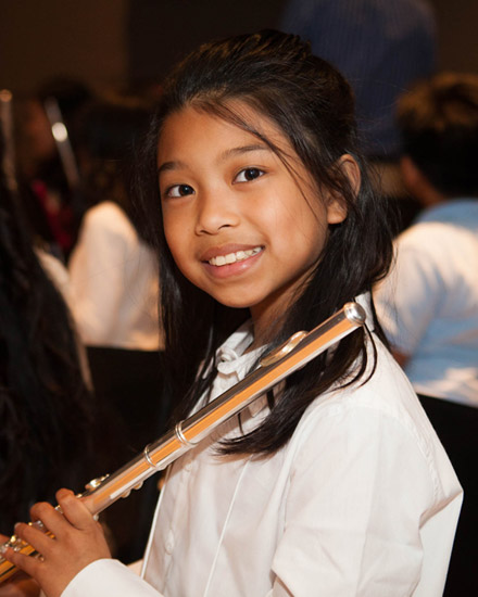 A young woman stands with a flute resting on her shoulder.
