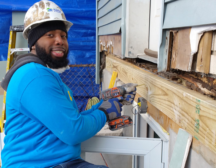 A volunteer home builder adding siding to a house.