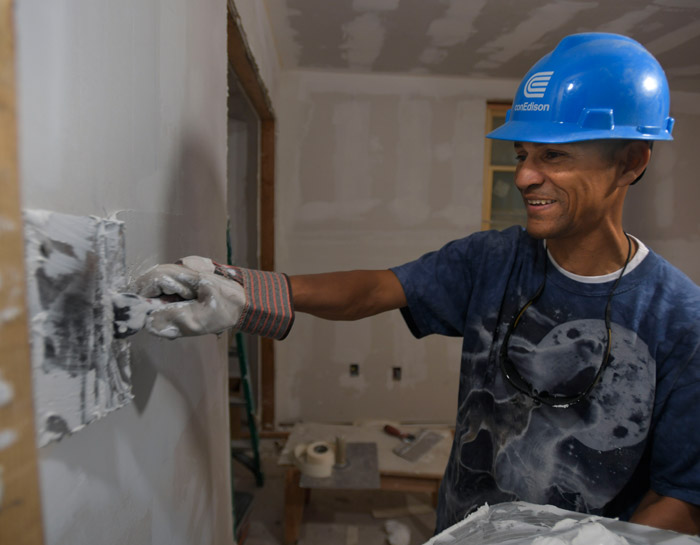A volunteer finishing a wall at a Habitat for Humanity event.